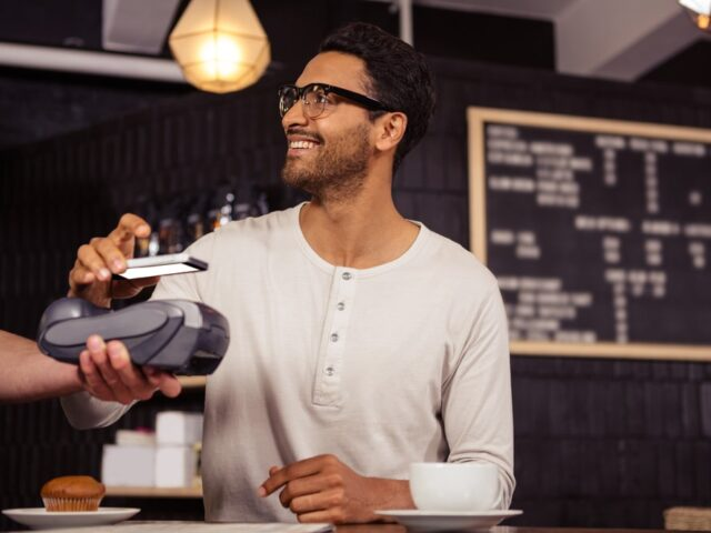 man with phone paying for his coffee
